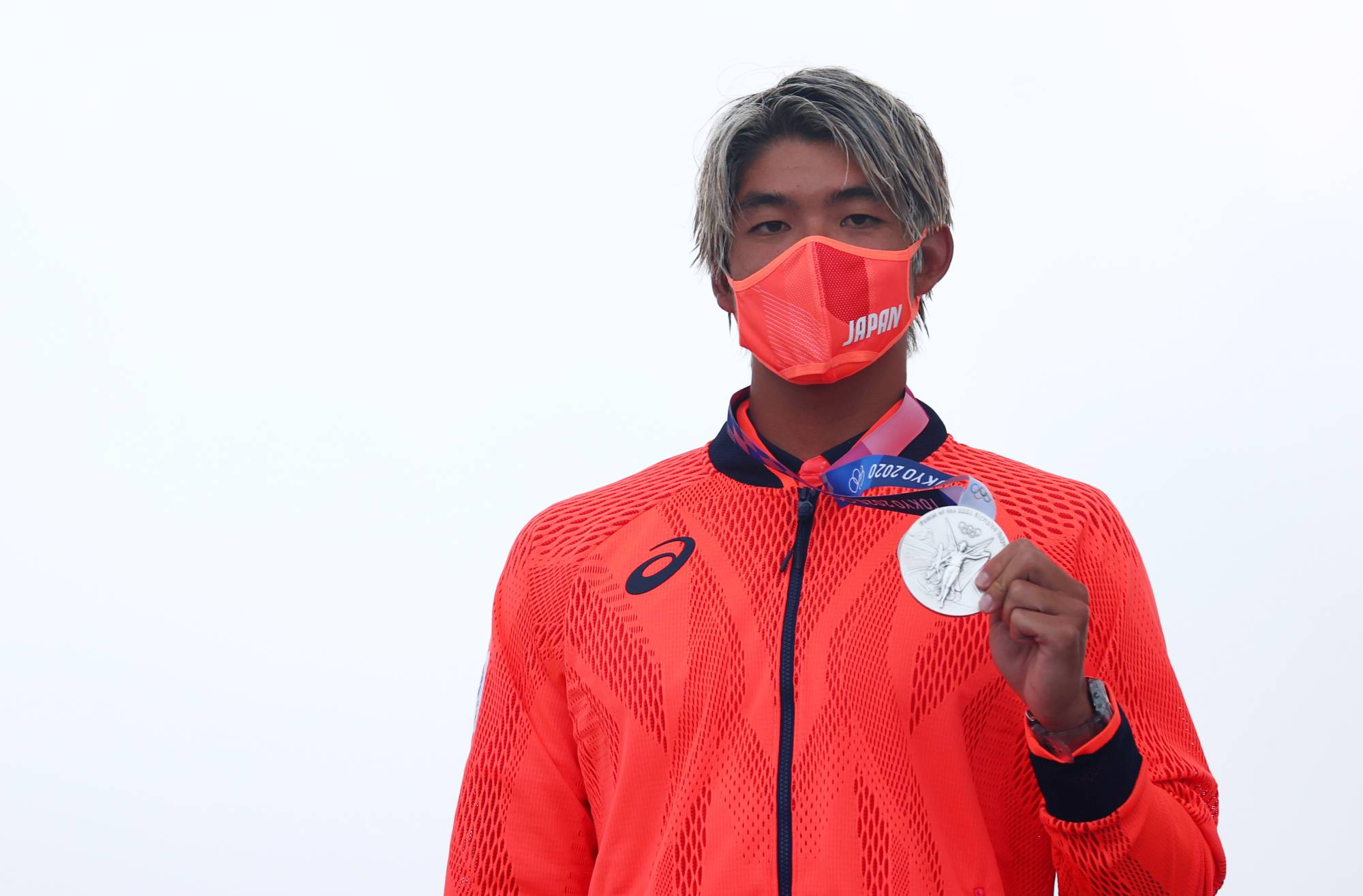 Tokyo 2020 Olympics - Surfing - Men's Shortboard - Medal Ceremony - Tsurigasaki Surfing Beach, Chiba, Japan – July 27, 2021. Silver medallist Kanoa Igarashi of Japan wearing a protective face mask poses on the podium REUTERS/Lisi Niesner